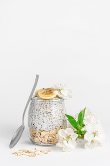 Чиа семена пудинг с йогуртом и овсом на белом столе, украшенные цветами. концепция супер-пупер. копировать пространство