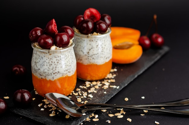 Chia seed yogurt pudding with sweet chrries, smashed fresh apricot and oats on black