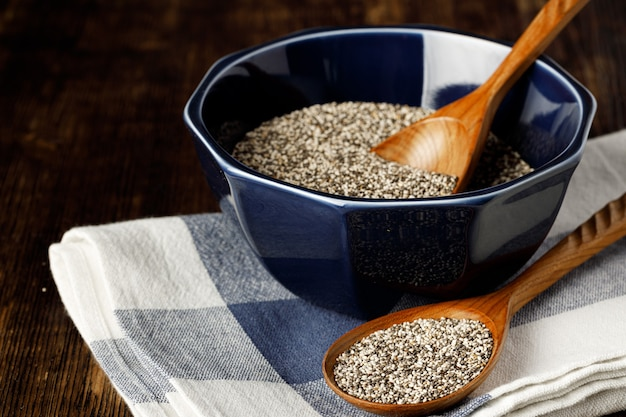 Chia seeds in a bowl with wooden spoon on wooden table