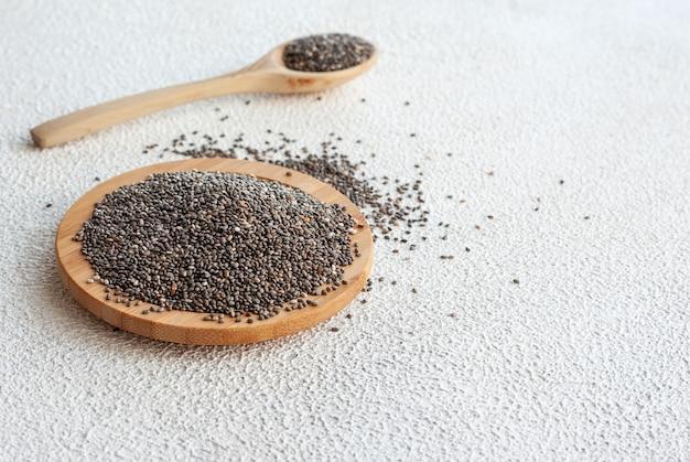 Семена чиа в деревянной тарелке на столе с ложкой