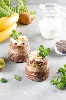 회색 테이블에 항아리에 초콜릿과 두유를 넣은 치아 씨앗 푸딩 제공