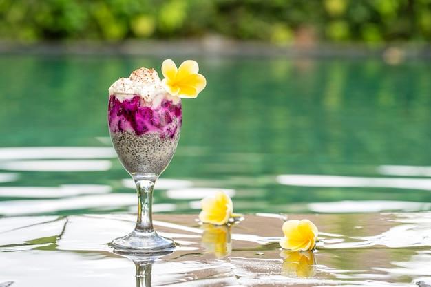 Пудинг из семян чиа с красным драконом и белым йогуртом в стакане на завтрак на фоне воды в бассейне, крупным планом. концепция здорового питания.