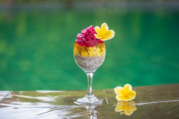 Пудинг из семян чиа с красным драконом, маракуйей, манго и авокадо в стакане на завтрак на фоне воды в бассейне, крупным планом. концепция здорового питания.
