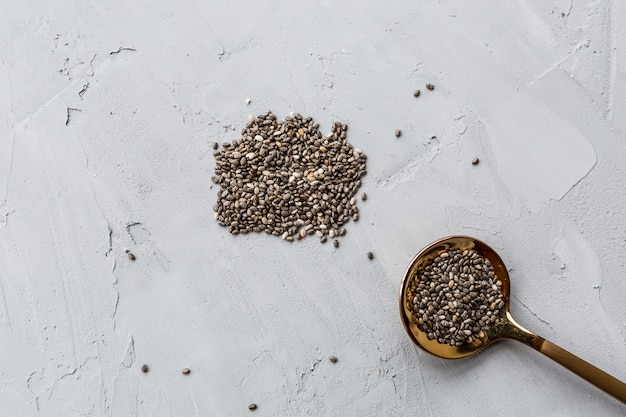 Chia seeds in spoon lying on gray concrete background.