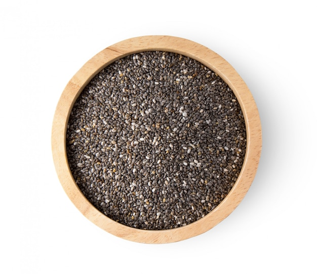 Chia seeds in wooden bowl on white wall.