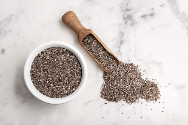 Chia seeds in wooden scoop and bowl on marble table. salvia hispanica. copyspace, top view
