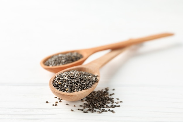 Chia seeds and wooden spoons on white wooden