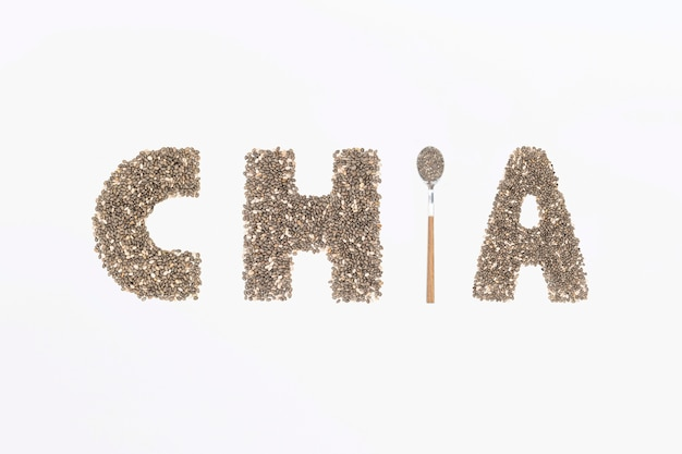 Chia word made from chia seeds with spoon full of seed on white background.