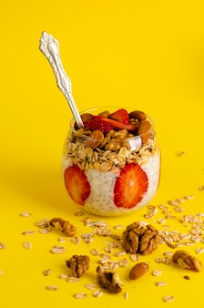 Пудинг цзя-йогурта с клубникой, овсянкой и орехами в стакане на желтом