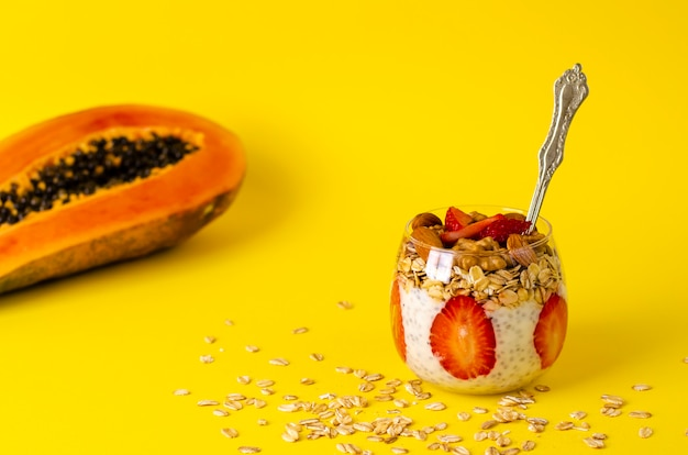 Chia yogurt pudding with strawberries, oatmeals and nuts in a glass on  yellow