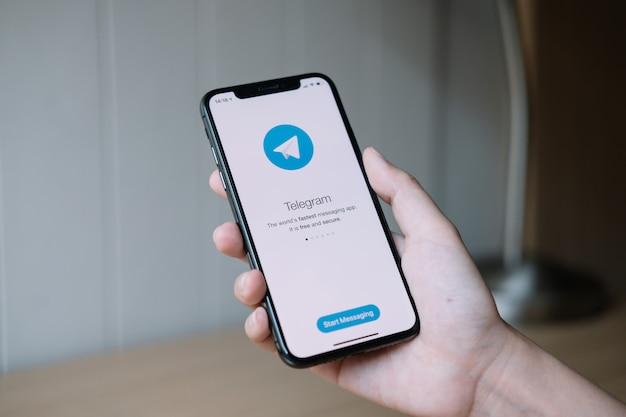 Чиангмай, таиланд, 22-ое июня 2020: рука женщины держа iphone x с telegram обслуживания социальной сети на экране. iphone 10 был создан и разработан apple inc.