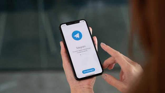 チェンマイ、タイ、2021年10月3日:画面にソーシャルネットワーキングサービスtelegramを搭載したiphonexを持っている女性の手。 iphone 10は、appleinc。によって作成および開発されました。