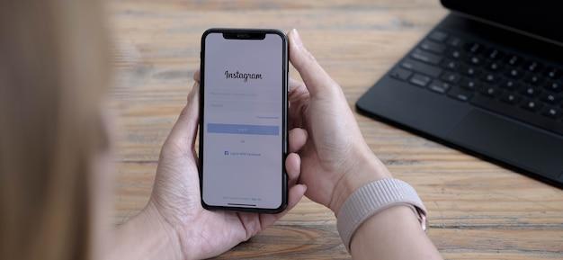 タイ、チェンマイ-2021年9月24日:女性が画面にinstagramアプリケーションを搭載したapple iphonexを持っています。 instagramはスマートフォン向けの写真共有アプリです。