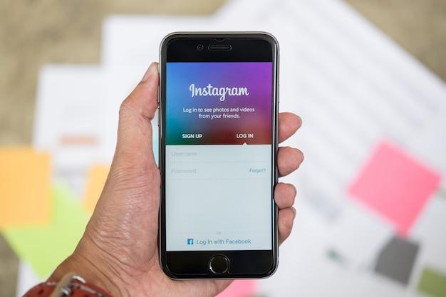치앙마이, 태국 -9 월 26 일, 2017 : 남자 손을 잡고 instagram 응용 프로그램의 로그인 화면으로 아이폰. instagram은 가장 크고 가장 인기있는 사진 소셜 네트워킹입니다.
