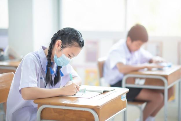 2021년 3월 2일 태국 치앙라이: 초등학교 학생들이 코로나바이러스 발병 기간 동안 교실에서 보호 마스크를 착용하고 시험을 치르고 있습니다.