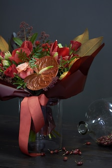 Chic autumn bouquet in red colors in vintage style in a glass vase and a huge jar of dry rose hips on dark