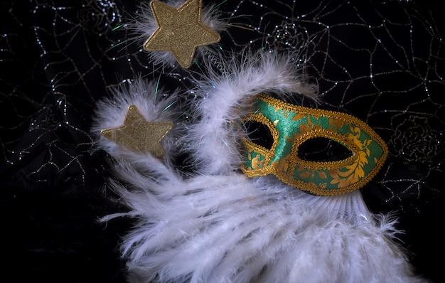 金色の星とカーニバルのための白い羽の背景を持つシックな緑と金色のマスク