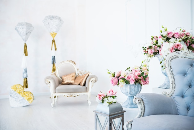 The chic interior and cozy atmosphere in an empty living room with armchairs with flowerpots and decor