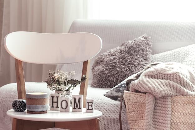家のシックなインテリア。キャンドル、白い木製の椅子に家の木製の文字が付いている花が付いているつぼ。バックグラウンドにクッションが付いたソファーと籐のバスケット。家の装飾。