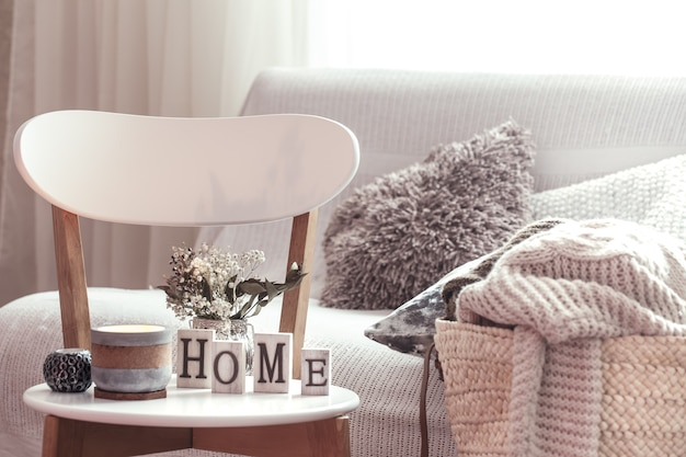 Chic interior for a house. candles, a vase with flowers with wooden letters of the home on wooden white chair. sofa and wicker basket with cushions in the background. home decoration.