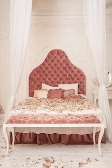 枕から羽が散らばったシックなレトロなキングサイズのベッド、部屋で枕の戦い。