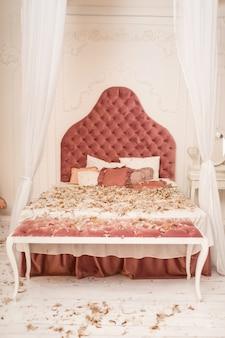 枕から羽が散らばったシックなレトロなキングサイズのベッド。部屋で枕投げ