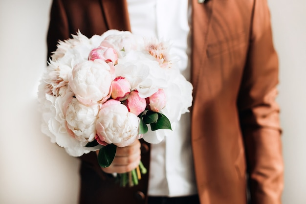 Chic wedding bouquet which the groom holds in a stylish brown suit