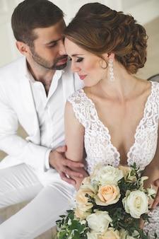 세련 된 웨딩 커플 신랑과 신부는 흰색 스튜디오에서 포즈. 웃 고 행복 한 커플입니다. 하얀 드레스. 흰색 정장. 청소년. 혼례. 샹들리에. 소파. 문.
