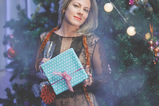Chic woman rejoices with a gift box near a christmas tree. a woman laughs, smiles, poses. special vintage noise and grain filter, blurry lights.