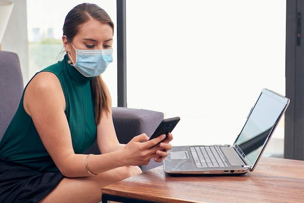 Chica latina con mascarilla enviando mensajes con su telefono movil