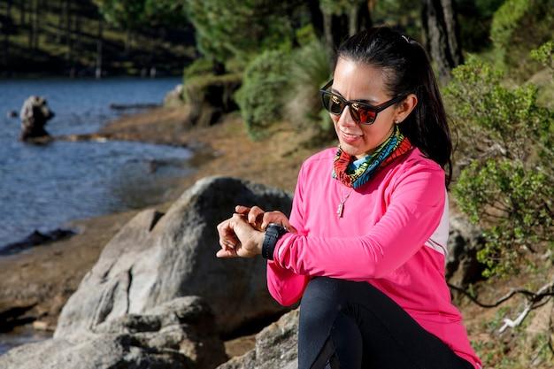 Chica revisando su reloj inteligente a la orilla de un lago despues de correr