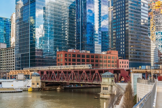 Chicago river walk with yacht running and traing running over the rail track usa