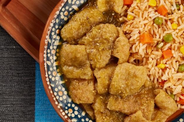 Chicharron en salsa verde con arroz rojo servido en plato de barro mexicano