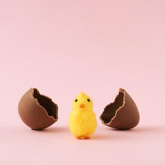 Цыпленок вылупился из шоколадного пасхального яйца на пастельно-розовой стене. минимальная концепция праздника.