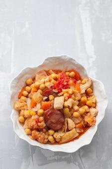 아름다운 그릇에 양배추, 당근, 훈제 소시지와 병아리 완두콩