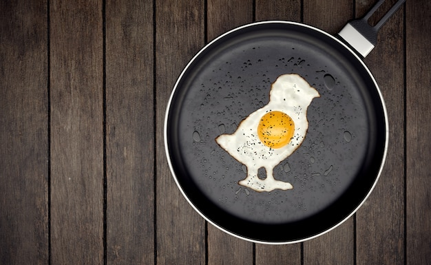 Chick-shaped fried egg in a pan on wooden