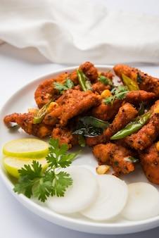Chicken 65 острый жареный во фритюре закуска или быстрая закуска из индии в миске или тарелке над белым