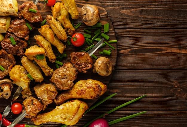 토마토와 파 나무 테이블에 닭고기와 쇠고기 꼬치.