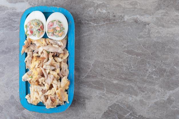 파란색 접시에 샐러드와 닭고기와 삶은 계란.