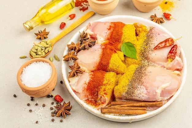 チキンとカレーのスパイス。伝統的な料理を調理するための原材料のセット。明るい石のコンクリートの背景、クローズアップ