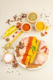 チキンとカレーのスパイス。伝統的な料理を調理するための原材料のセット。明るい石のコンクリートの背景、上面図