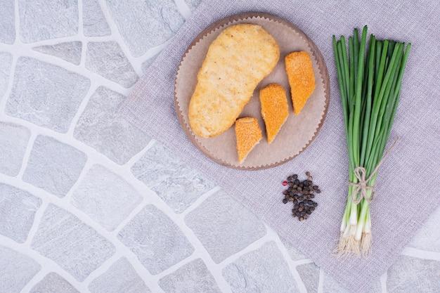 녹색 양파의 무리와 함께 나무 보드에 닭고기와 생선 덩어리.