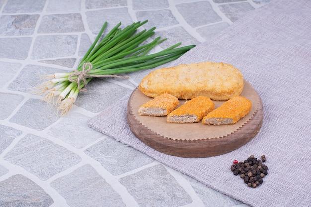 양파 뭉치와 함께 제공되는 닭고기와 생선 덩어리.
