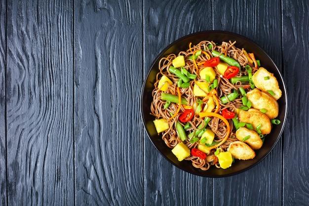 나무 테이블에 검은 그릇에 찐 녹두, 잘게 썬 당근, 칠리 페퍼, 봄 양파를 곁들인 치킨과 망고 소바 누들 샐러드, 위에서 볼 수 있습니다.