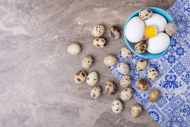 Куриные и перепелиные яйца в голубой чашке.