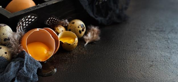 暗い背景のボックスに鶏とウズラの卵