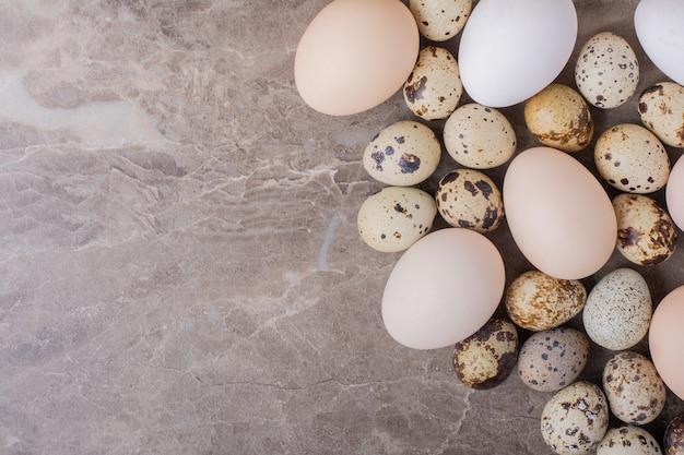 Куриные и перепелиные яйца на мраморе.