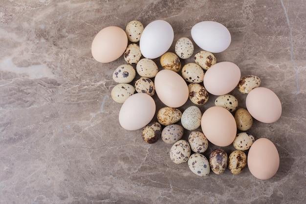 Куриные и перепелиные яйца на каменной поверхности