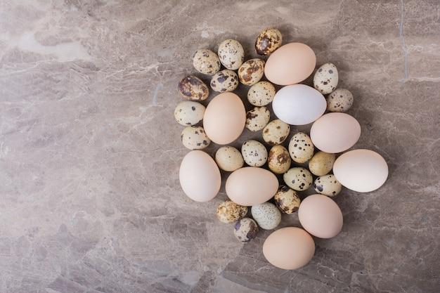 돌 표면에 닭고기와 메추라기 알