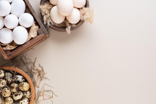 Куриные и перепелиные сырые яйца на бежевый стол.